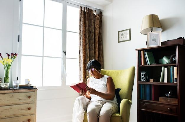 年配の女性が部屋で本を読んで