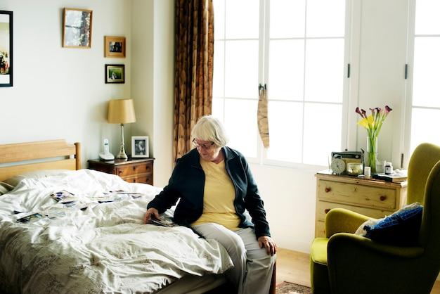年配の女性がベッドの上に座って