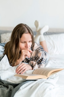 Кавказская женщина читает книгу в постели