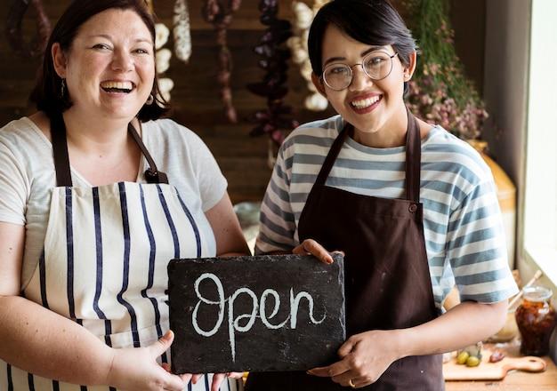 オープンサインを示す陽気なデリショップのオーナー