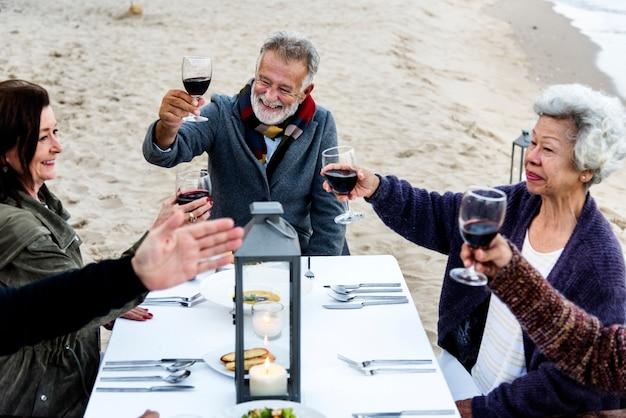 高齢者のビーチで赤ワインで乾杯
