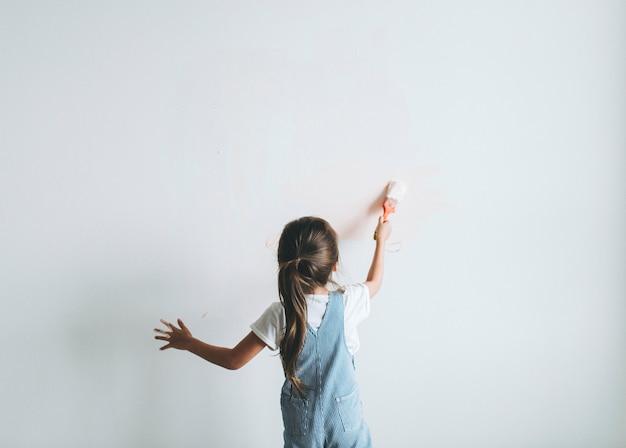 Молодая девушка красит стены в розовый цвет