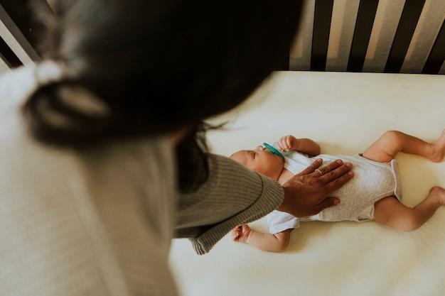眠っている赤ちゃんの世話をしている母親