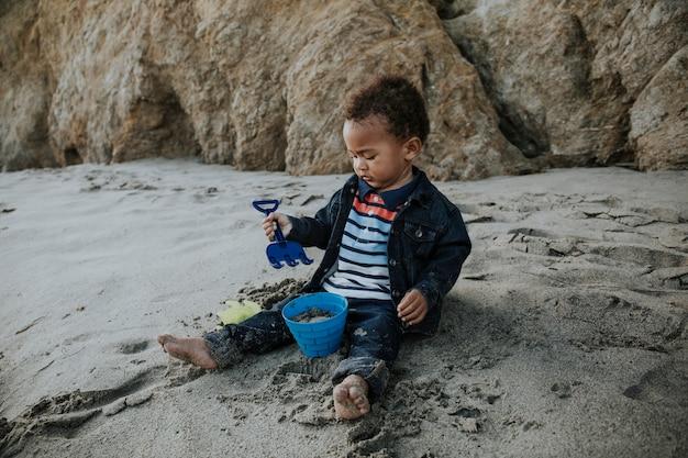 小さな男の子がビーチで遊んで