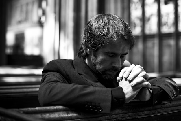 教会で祈っている孤独なクリスチャン男