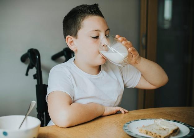 ミルクのガラスを飲む少年