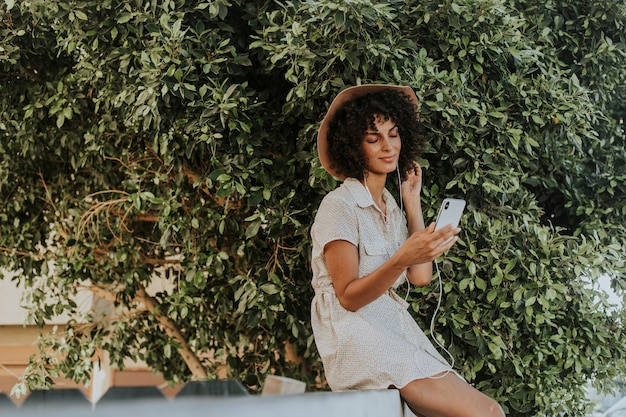 Красивая женщина слушает музыку в ботаническом саду