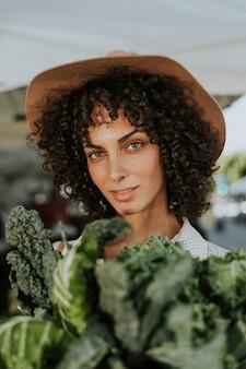 美しい女性が農民市場でケールを買う