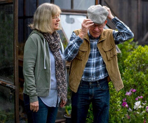 庭の裏庭で野菜を植える年配のカップル