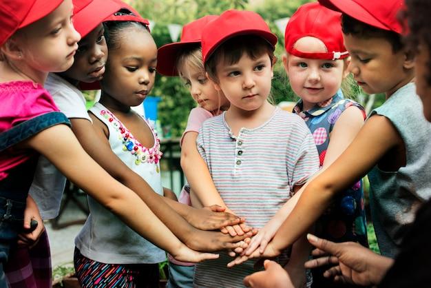 多様な子供たちのグループが一緒に手を差し伸べるチームワーク