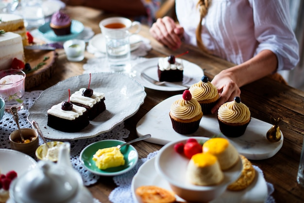 甘いデザートケーキを楽しんでいる女性