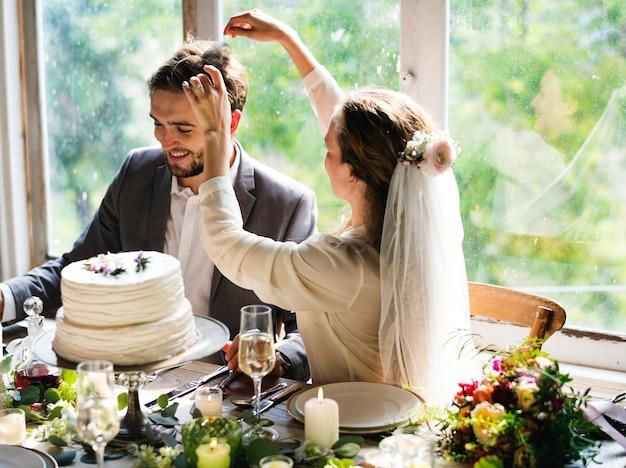 新郎の髪とレセプションテーブルで遊ぶ花嫁