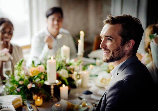 新郎の結婚披露宴のテーブルでスピーチを聞いて