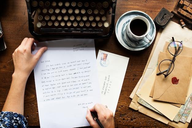 空撮の木製テーブルの上の手紙を書く手