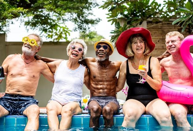 一緒に夏を楽しんでいるプールのそばに座っている多様な高齢者のグループ
