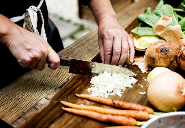 玉ねぎを刻んでナイフで手のクローズアップ