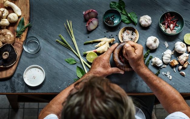 乳鉢と乳棒でアジアの食材を粉砕する手の航空写真