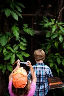 カメラで写真を撮る若い白人の女の子の背面図