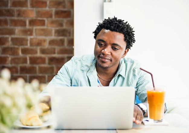 アフリカ系の男がラップトップを使用しています