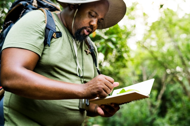 彼のメモ帳でメモを作っている植物学者