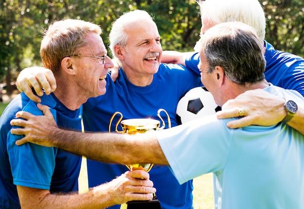 カップを獲得した成熟したフットボール選手のチーム