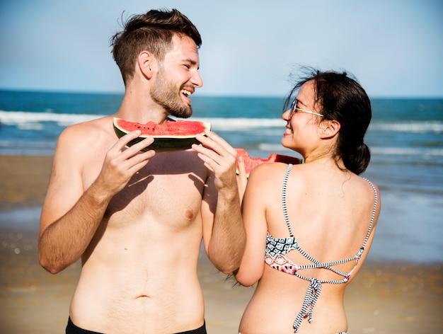 カップルはビーチでスイカを食べる