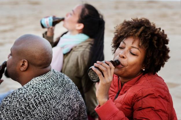 ビーチでビールを飲む友人