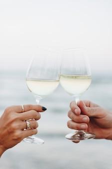 ビーチでワインのグラスを楽しむカップル