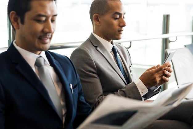 ビジネスの男性が座って新聞を読む