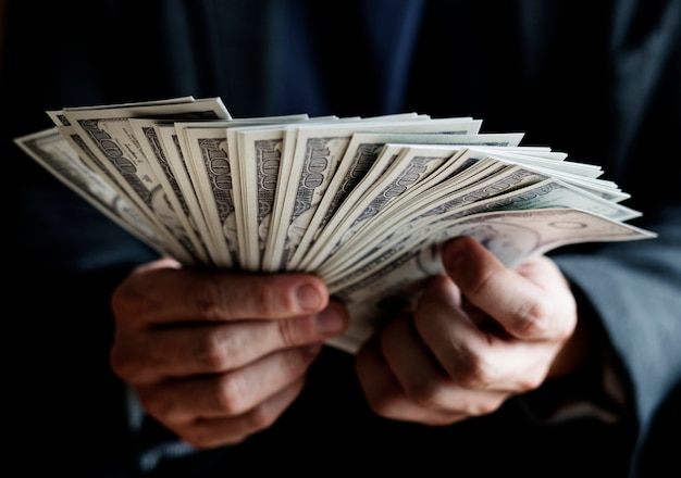 Макрофотография руки, держащей деньги