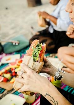 ビーチでサンドイッチを食べる女
