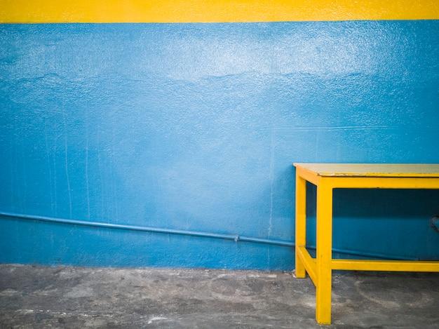 水色の壁に対して黄色のベンチ