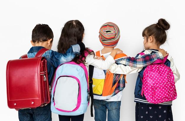 バックパックを身に着けている多様な子供たちの後姿グループ