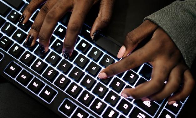 コンピューターのキーボードで作業する手のクローズアップ