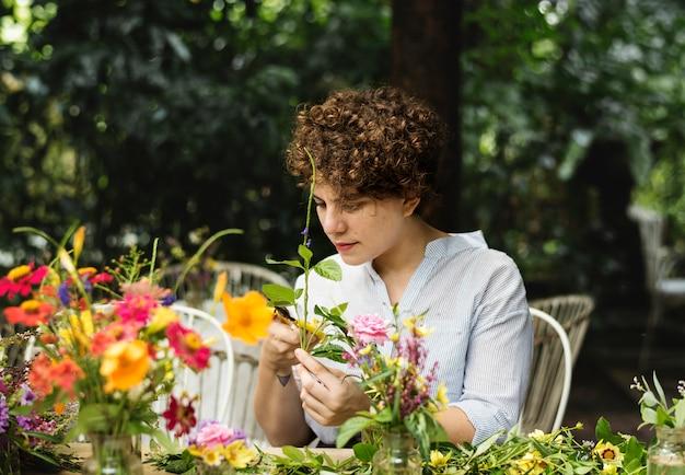 Женщина аранжирует и украшает цветы