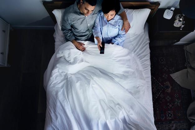 Межрасовые пары на кровати смотрят телевизор вместе