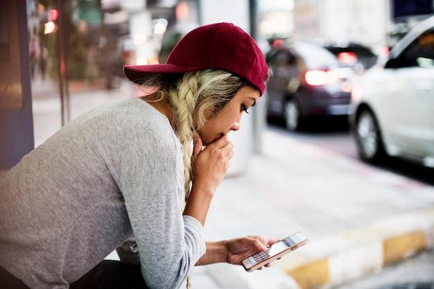 街の真ん中でスマートフォンを使用している深刻な女性