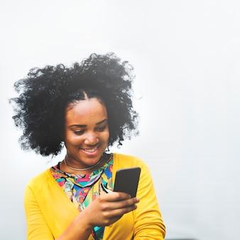 Молодая девушка улыбается во время текстовых сообщений
