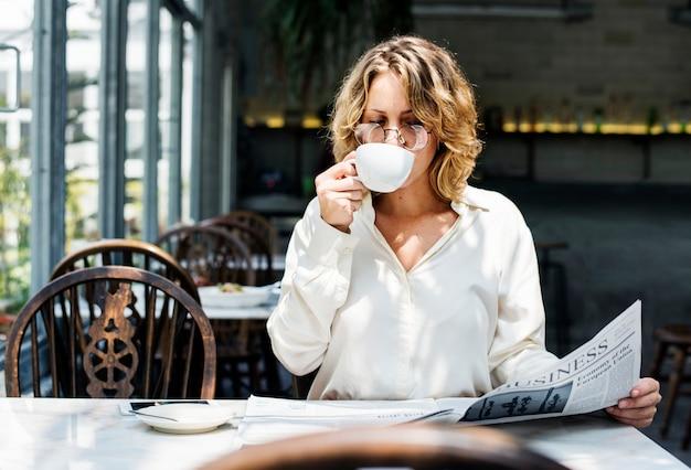 ビジネスの女性が午前中に新聞を読む