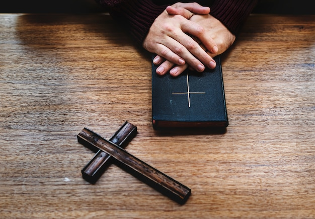 木製のテーブルの上の聖書を引き渡す