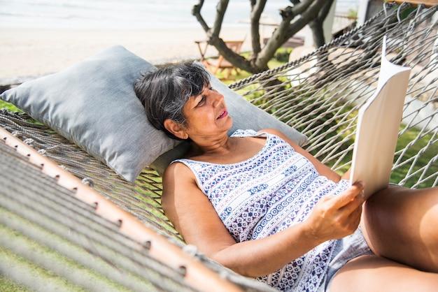 年配の女性がハンモックで雑誌を読む