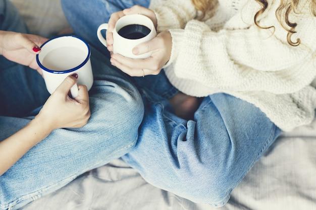 温かい飲み物のカップを保持している女性