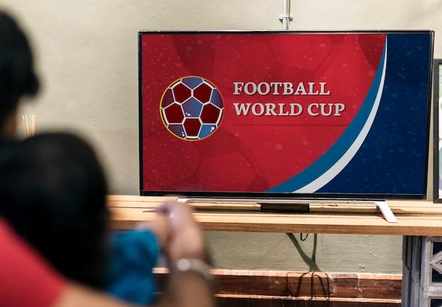 テレビでサッカーの試合を見ている家族