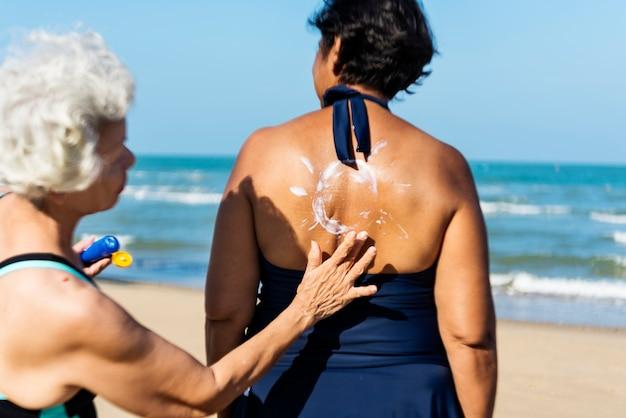 日焼け止めをするのを助ける女性