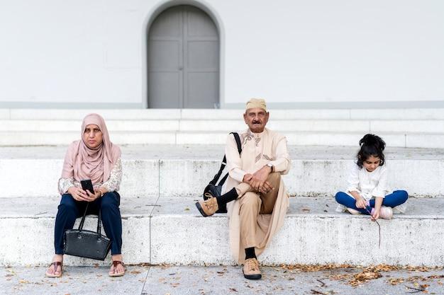 屋外一緒に座っているイスラム教徒の家族
