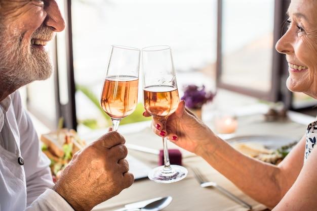 Веселая старшая пара выпивает шампанское