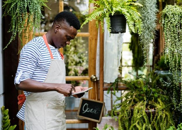 成人男性の花屋の外の植物をチェック