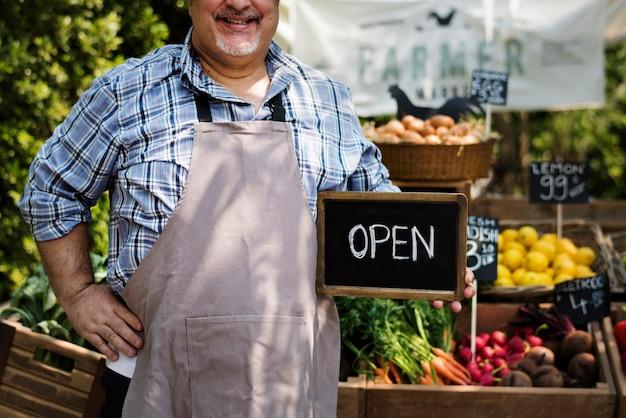 Человек владелец свежего продуктового органического магазина