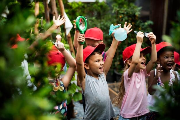 屋外の園芸を学ぶ幼稚園の子供たちのグループ