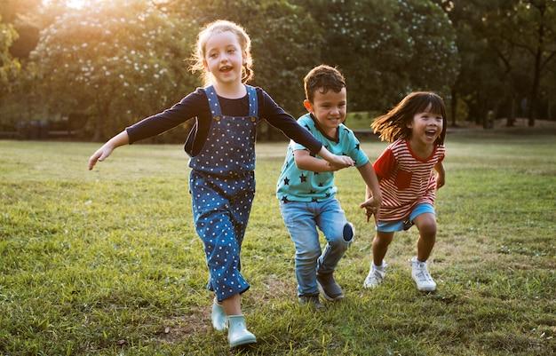 フィールドで一緒に手を取り合って多様な子供たちのグループ